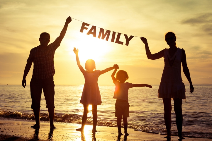 """Happy family standing on the beach at the sunset time. Parents hold in the hands inscription """"Family"""". Concept of happy family."""